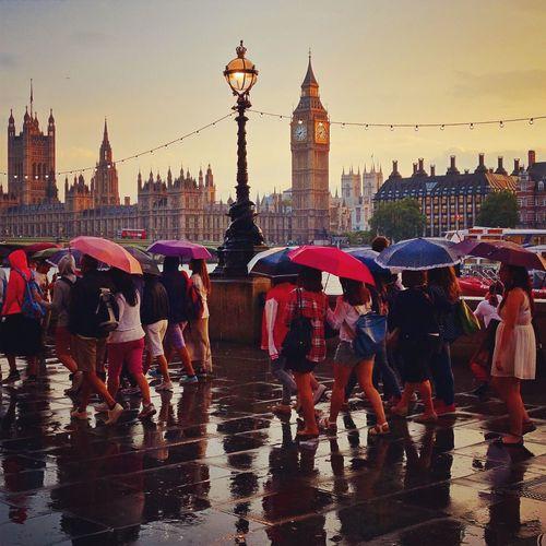 People walking on promenade by big ben during rainy season