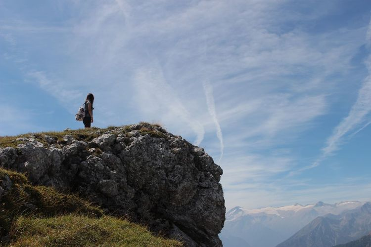Woman standing high up at edge of mountain