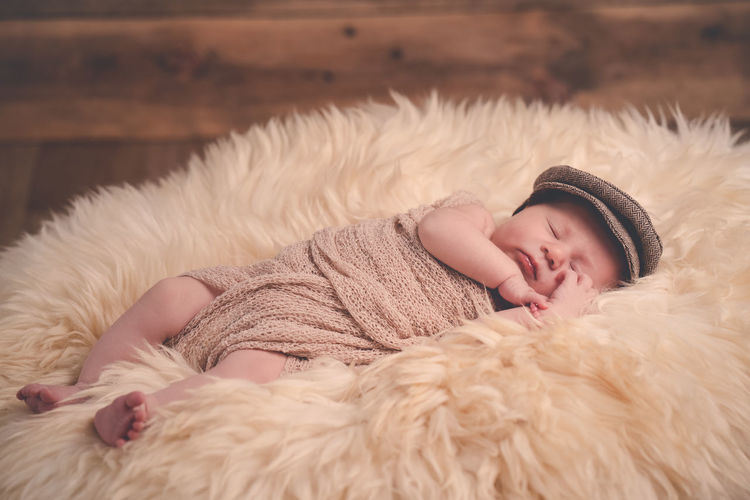 Newborn baby sleeping on coat Childhood Real People One Person Fur Child Lying Down Relaxation Innocence Eyes Closed  Young Cute Sleeping Babyhood Baby Indoors  Lifestyles Resting Clothing Warm Clothing Newborn Coat Beginnings Hat Baby
