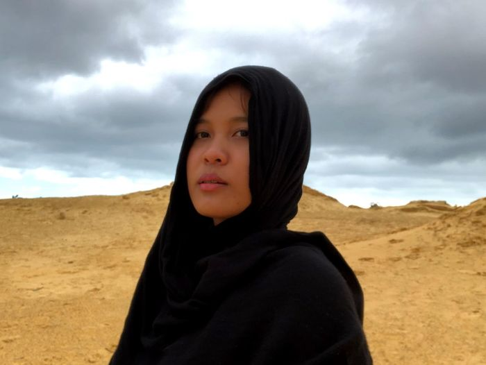 Portrait of young woman in hijab standing on land against cloudy sky