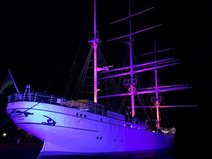 Low angle view of illuminated sailboat against sky at night