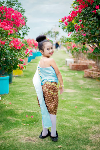 Little girl with Thai dress. Asian  Fashion Gold Makeup Slippers Thai Thai Dress Thailand Uniform Accessories Asian Girl Beautiful Woman Casual Clothing Child Childhood Day Field Flower Flowering Plant Full Length Girl Grass Growth Innocence Kid Leisure Activity Lifestyles Little Girl Loincloth Model Nature One Person Outdoors Plant Real People Smiling Standing Thai Style Vintage Women