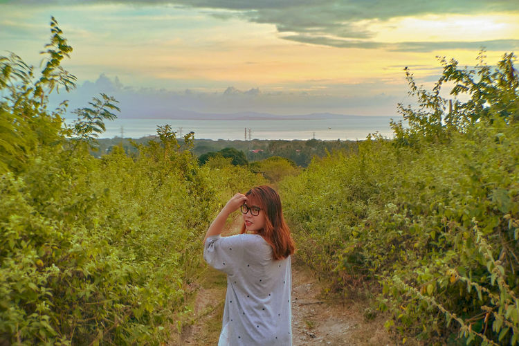 Woman standing by plants against sky during sunset
