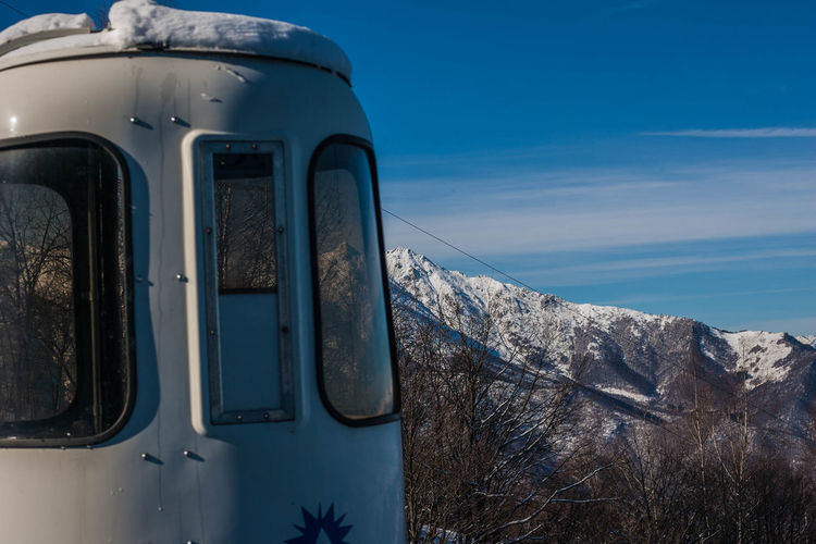 Close-Up Of Car On Snow Covered Mountain Against Sky