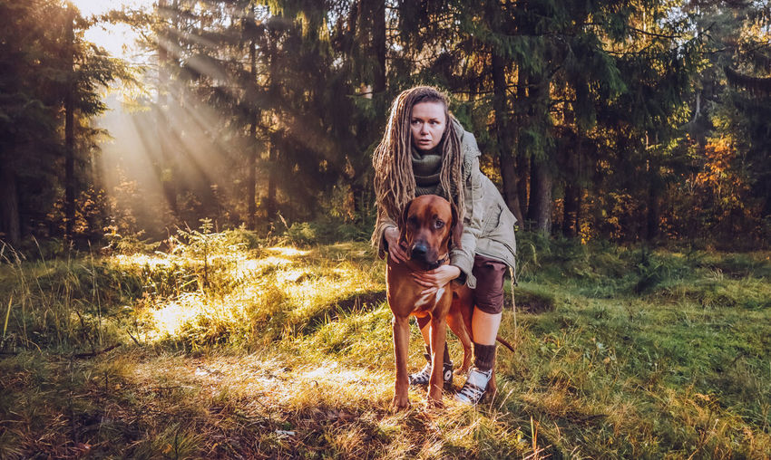 Young smiling woman with dreadlocks in autumn fall forest in the morning sunshine playing with a dog ridgeback Dog Canine Pets One Animal Domestic Animals Domestic Mammal Tree Animal Animal Themes Plant Land Real People Vertebrate Leisure Activity Front View Nature Young Adult Looking At Camera One Person Pet Owner Hairstyle Teenager Beautiful Woman Dreadlocks Ridgeback
