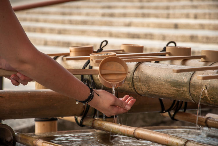 Cropped hands holding bamboo dipper at fountain