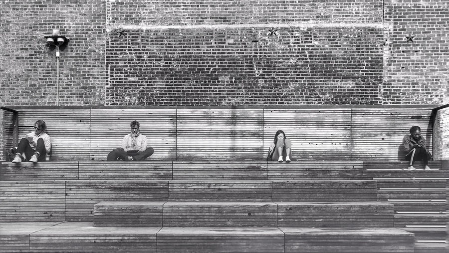 Group of people on brick wall