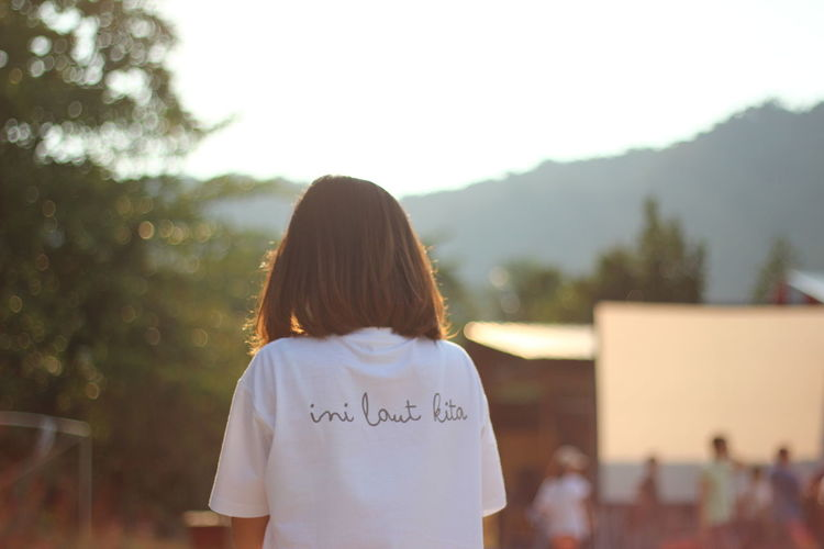 Rear view of woman wearing t-shirt with text against trees
