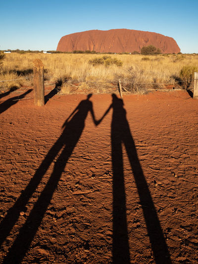Shadow of two people holding hands in front of uluru, the red centre of australia