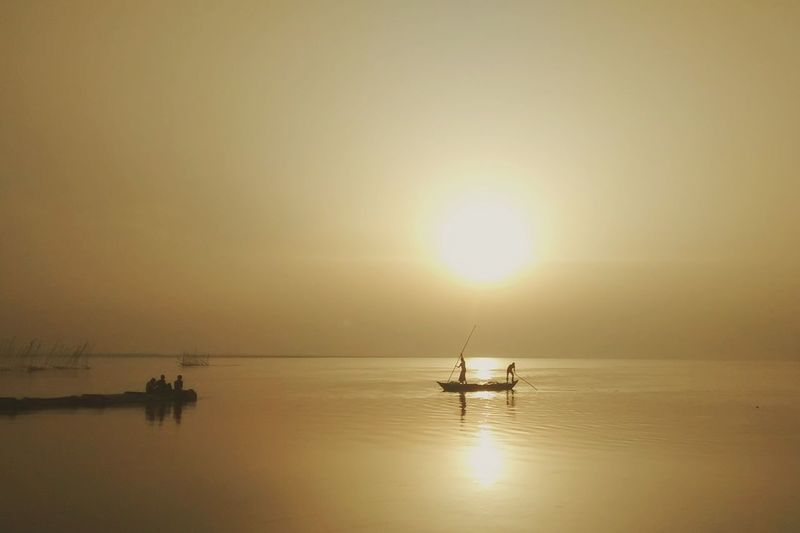 People sailing on boat in river against clear sky at sunset