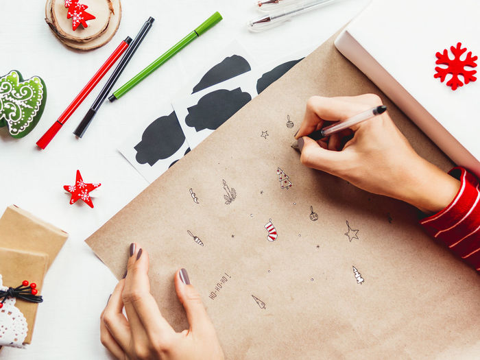 High angle view of woman drawing on paper