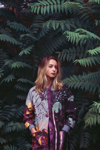 Portrait of young woman with hands in pockets standing amidst trees