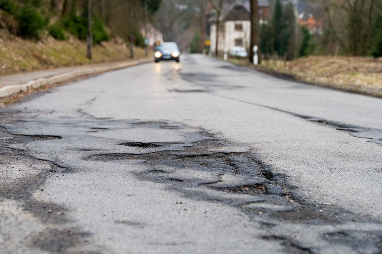 Pothole - Infrastructure degradation. Poor condition of the road surface. Hole in the asphalt Transportation Road Mode Of Transportation Motor Vehicle Direction Car City Land Vehicle The Way Forward Street Asphalt Day Surface Level Nature No People Tree Sign Selective Focus Plant Symbol Outdoors Pothole Pot Hole Traffic Asphalt Damage