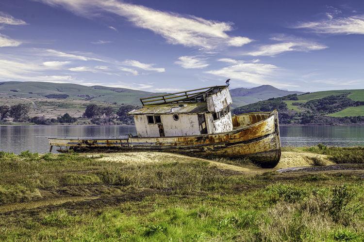 Abandoned boat on land against sky