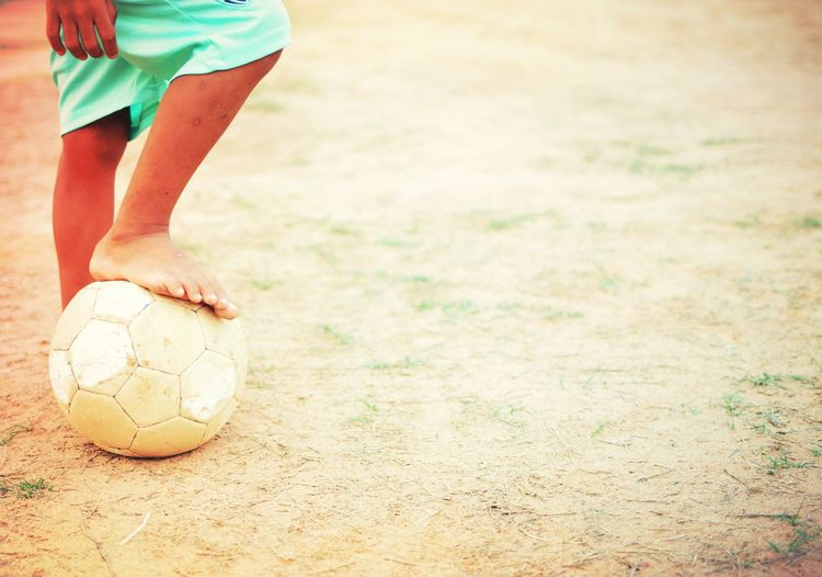 Low section of boy playing soccer ball
