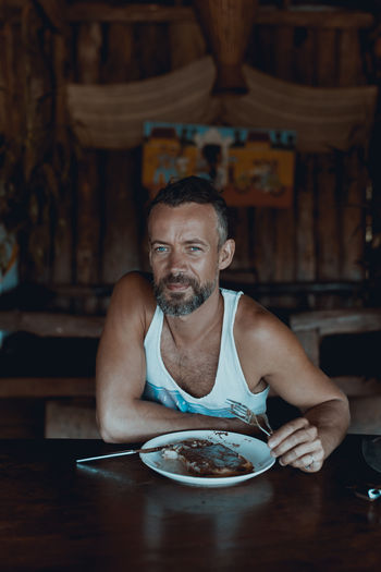 Portrait Of Man Having Food At Table