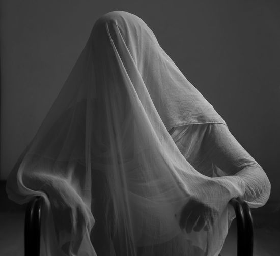 Person covered with fabric sitting on chair