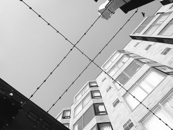 Wired City Architecture Low Angle View Building Exterior Built Structure Outdoors No People Electricity  Day Sky Black And White Black & White Straight Lines String Of Lights Streetphotography PhonePhotography Phone Mobile Editing