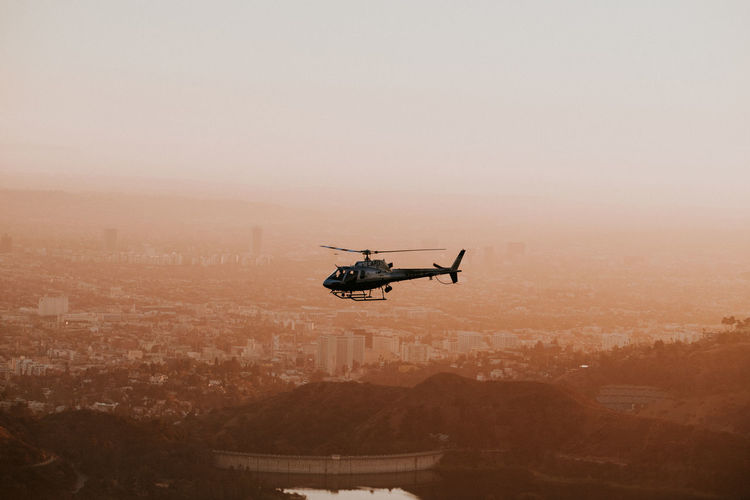 Helicopter Flying Over City During Sunset