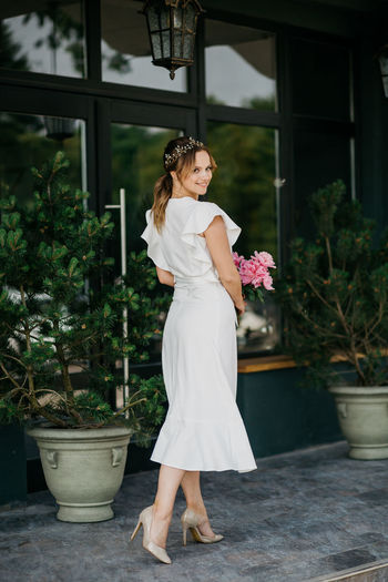 Full length of woman standing by potted plant