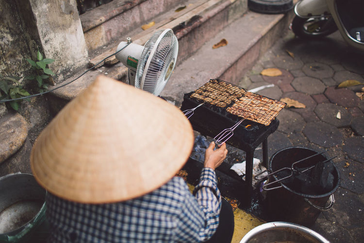 Rear view of man preparing food on street