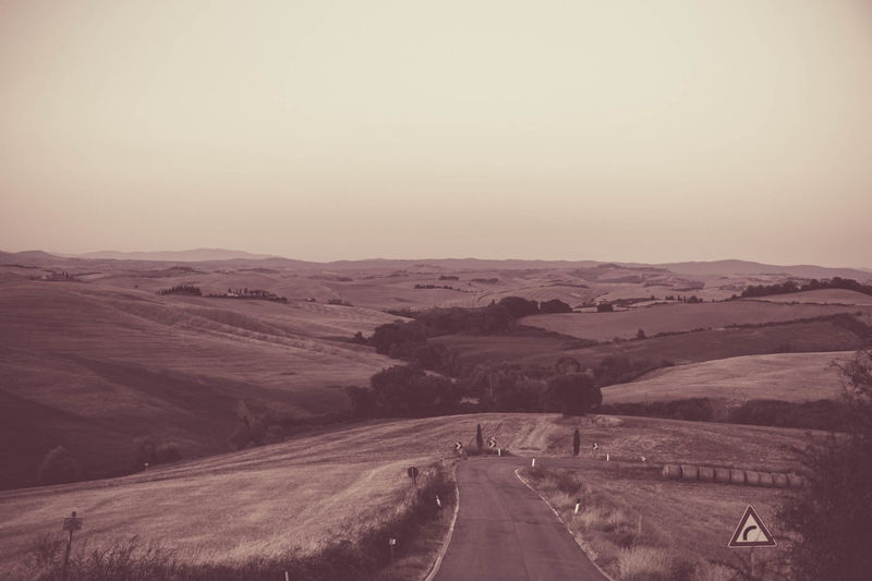 Road leading towards desert against clear sky