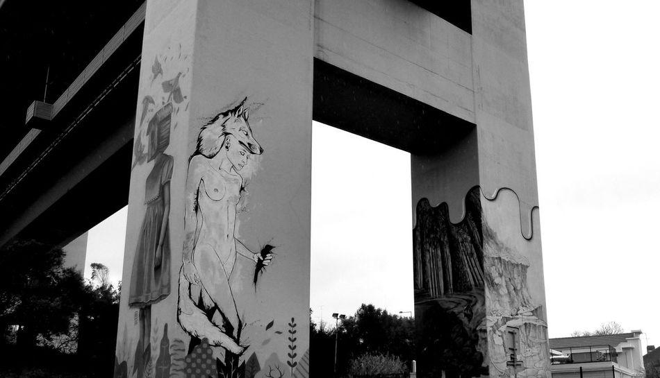 A graffiti drawing under the bridge April 25 Lisbon Portugal, street art designs Architecture Art Designs Black & White Black And White Blackandwhite Photography Bridge Bridge - Man Made Structure Built Structure Designs Graffiti Graffiti Art Outdoors Sky Street Art Street Art/graf Street Art/Graffiti