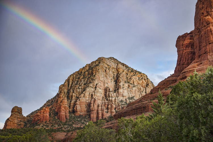 Low Angle View Of Rainbow Over Rock Formation