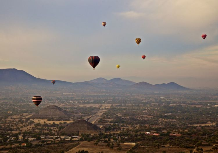 High angle view of hot air balloons flying over landscape