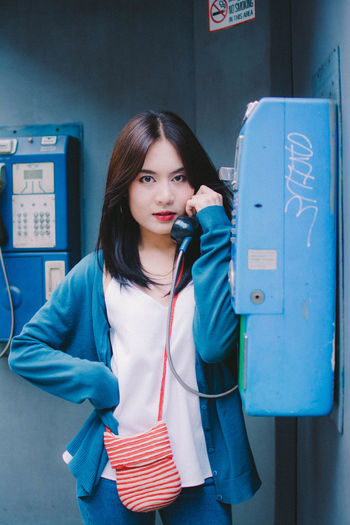 Portrait of young woman talking over telephone