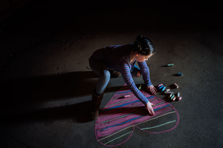 High angle view of girl making heart shape with chalk on floor