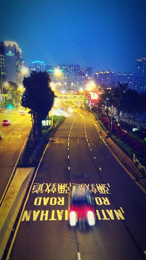 Illuminated city street against clear sky at night