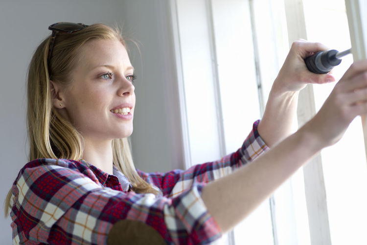 Portrait of young woman holding camera while looking through window