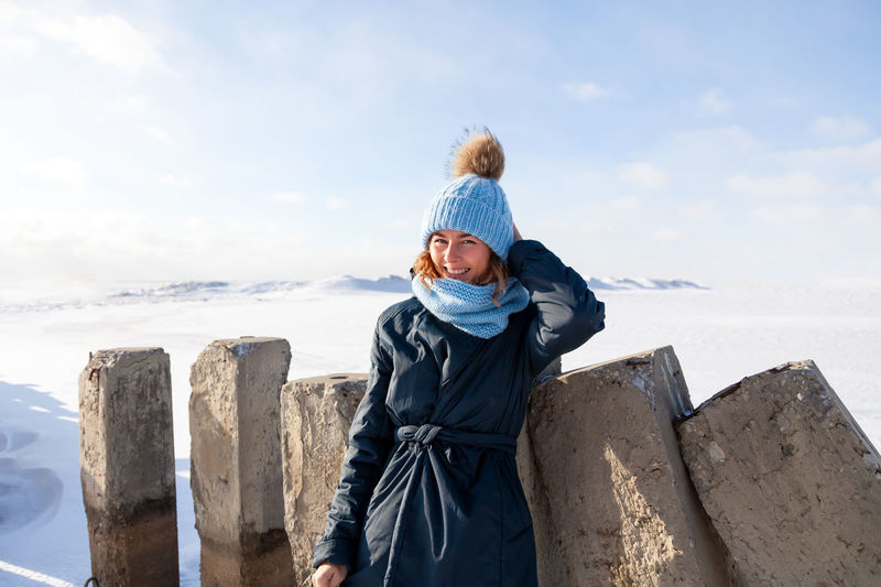Close up portrait of beauty woman in frosty stylish coat around frozen sea and stone