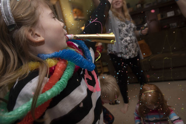 A seven-year-old girl blows a noise maker during New Year's Eve at her home with her family. New Year's Eve New Year's Eve 2019 Family Celebration Party Togetherness Happiness Confetti Dancing Action Fun Indoors  Lifestyles Leisure Activity Bonding Moments Of Happiness 2018 In One Photograph
