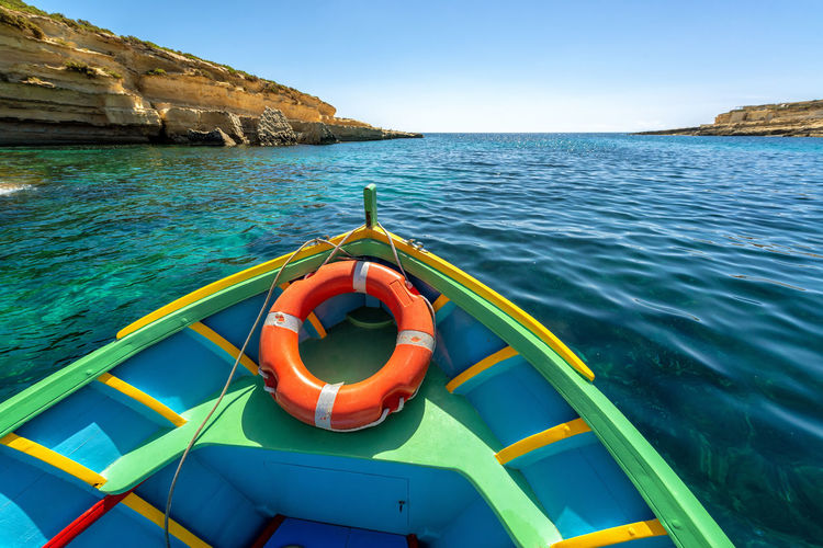 Rowboat Sailing In Sea Against Clear Blue Sky