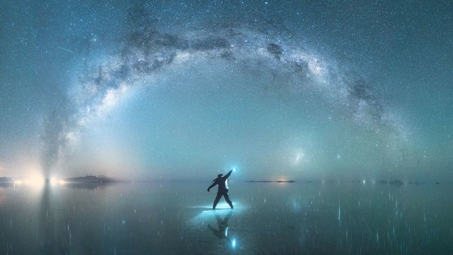 Rear view of man standing against star field in sky at night