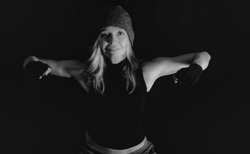 Portrait of woman flexing muscles against black background