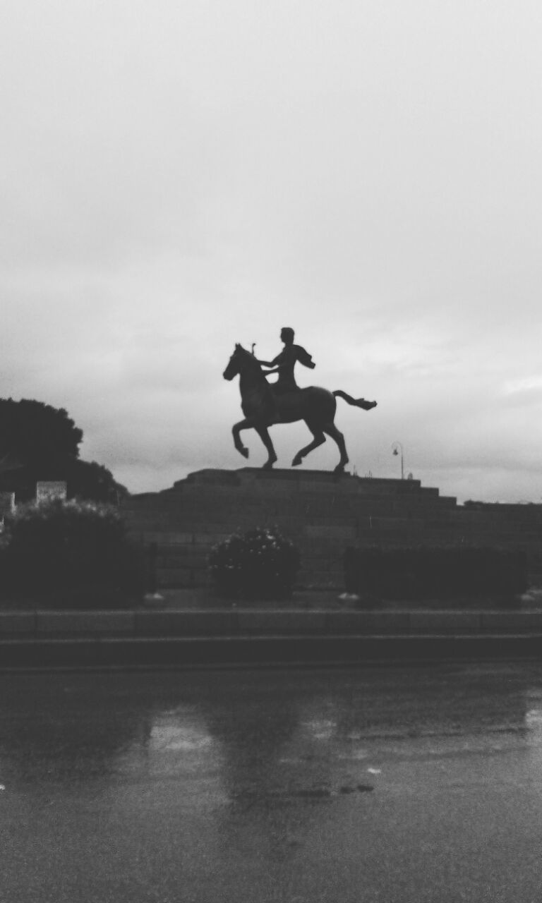 sky, statue, water, silhouette, outdoors, sculpture, men, waterfront, horseback riding, cloud - sky, day, nature, people