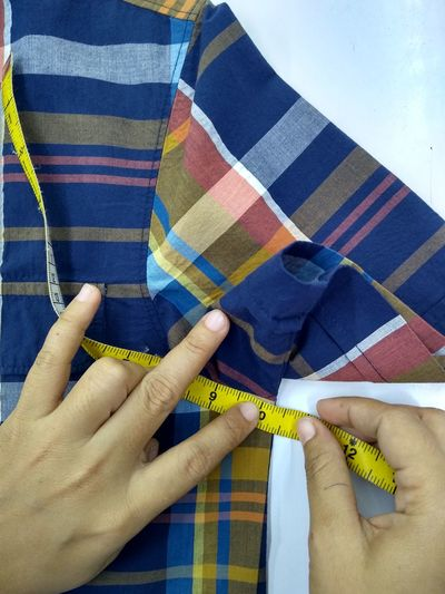Cropped hand of woman measuring textile