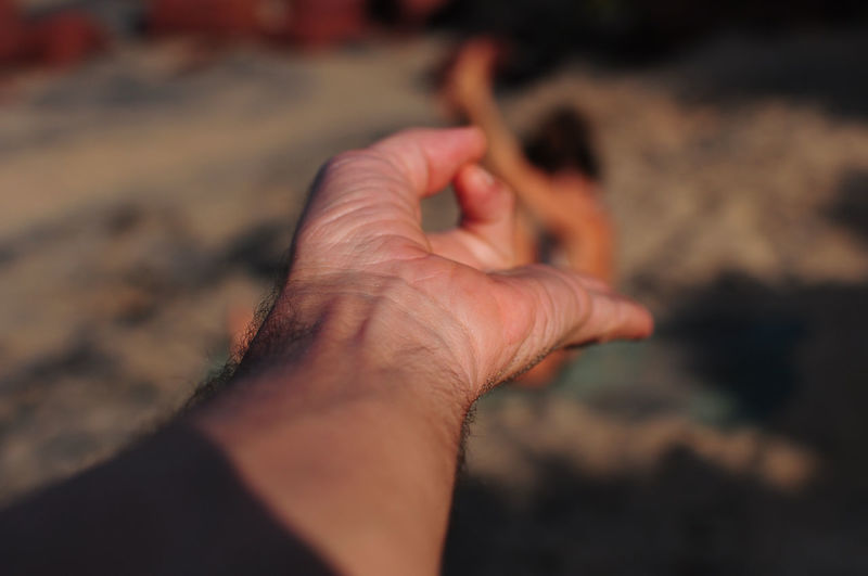 Cropped hand of man gesturing at beach