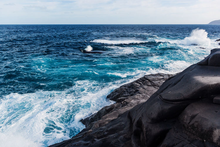 Waves breaking on the rocky coast of the canary islands. tourism, travel, vacation, sea cruise.