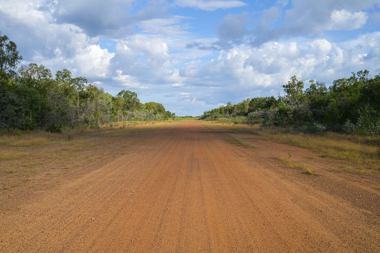 Dirt road amidst trees on field against sky