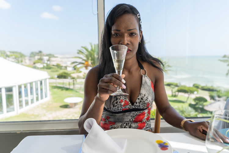 young woman toasting with champagne Adult Day Drink Drinking Focus On Foreground Food And Drink Front View Glass Hairstyle Holding Leisure Activity Lifestyles One Person Outdoors Portrait Real People Refreshment Table Women Young Adult Young Women