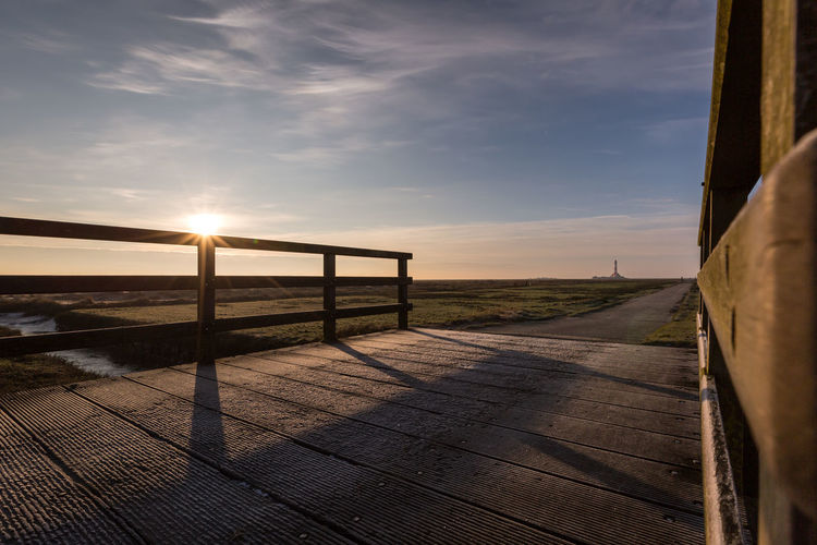 Footpath by railing against sky during sunset
