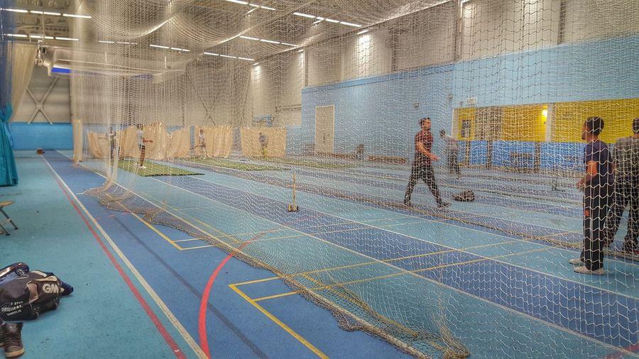 Cricketers practicing indoors