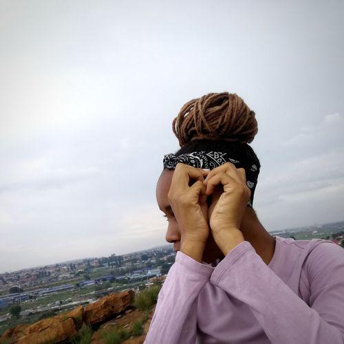 Woman with dreadlocks against sky