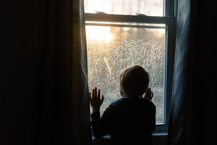 Rear view of boy looking through window