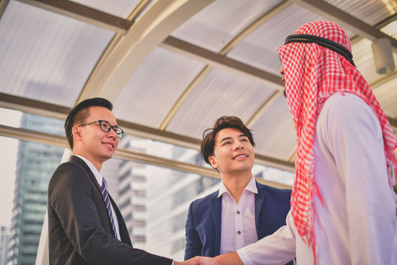 Businessmen shaking hands while client on elevated road