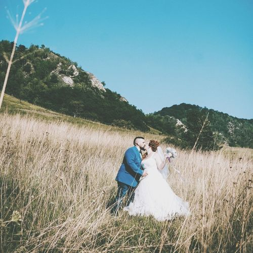Rear view of wedding couple on field against clear blue sky